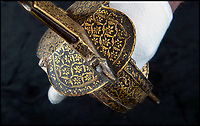 BNPS.co.uk (01202) 558833<br /> Pic: PhilYeomans/BNPS<br /> <br /> History in his hands - Tipu Sultans sword complete with ornate gold inlay.<br /> <br /> Stunning artefacts from Indian hero Tipu Sultan's fateful last stand have been rediscovered by the family of an East India Company Major who took part in the famous battle that ended his reign.<br /> <br /> And now Major Thomas Hart's lucky descendents are likely to become overnight millionaires after retrieving the historic items from their dusty attic.<br /> <br /> The fascinating treasures were taken from Tipu's captured fortress of Seringapatam in the wake of his defeat by British forces led by a young Duke of Wellington in 1799.<br /> <br /> The cache of ornate gold arms and personal effects even include's the battle damaged musket the Sultan used in his fatal last stand against the expanding British Empire in India.<br /> <br /> Tipu was last seen on the battlements of the fortress firing his hunting musket at the advancing British and after the fierce encounter his body was found bearing many wounds, including a musket ball shot above his right eye.<br /> <br /> The rediscovered musket, complete with battle damaged bayonet, has the distinctive tiger stripe pattern unique to the self styled Tiger of Mysore own weapons - and tellingly there is also shot damage to the lock and stock that may have been caused by the musket ball that finished him off.<br /> <br /> Also included in the sale are four ornate gold-encrusted sword's bearing the mark of Haider Ali Khan, Tipu's father and the previous ruler of independent Mysore, along with a solid gold &lsquo;betel casket&rsquo; complete with three 220 year old nuts still inside.<br /> <br /> The war booty was brought back to Britain by Major Thomas Hart of the British East India Company following the fourth and final Anglo-Mysore war.<br /> <br /> They have been passed down through the family ever since and now belong to a couple who have kept them wrapped in newspaper in the dusty attic of their semi-detached home for years.
