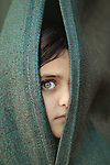 A girl with green eyes cover her face. Photo by Sanad Ltefa