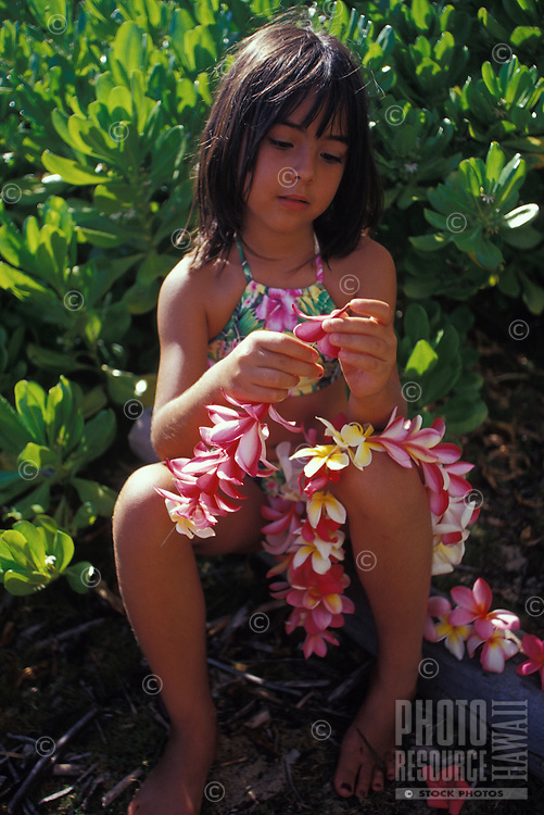 Young local Hawaiian girl making plumeria Leis of red, white, and pink flowers, Waialua, Hawaii.