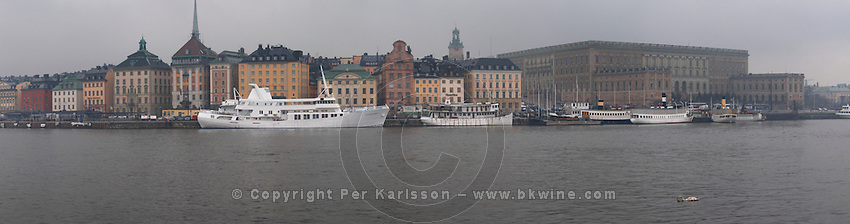 The Swedish Royal Palace in the Gamla Stan, Old Town. In foggy winter weather. White Waxholm boats Waxholmsbatar typical for the archipelago traffic. Stockholm. Sweden, Europe.