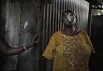 """Aicha regarde par la fenêtre de son banga de tôle, une ouverture faite à la machette plus qu'une réelle fenêtre. Aicha espère trouver un travail lorsqu'elle aura ses papiers et habiter dans une """"vraie"""" maison, Labattoir, Mayotte, octobre 2016."""
