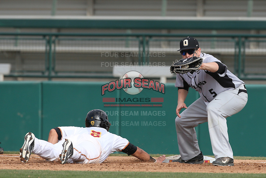Zach Sterry (5) of the Oakland Grizzlies catches a throw as Jeremy Martinez (2) of the Southern California Trojans slides back to first base during a game at Dedeaux Field on February 21, 2015 in Los Angeles, California. Southern California defeated Oakland, 11-1. (Larry Goren/Four Seam Images)