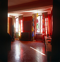 A dramatic red room with floor to ceiling curtains and a hexagonal tiled floor. Large coloured glass lights hang at one window.