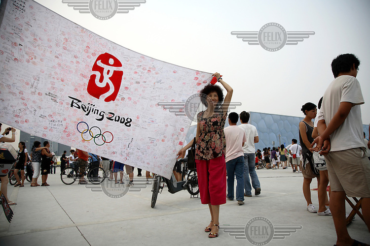 A woman holds up a Biejing Olympic Games flag in front of the National Aquatics Centre, or the Water Cube.