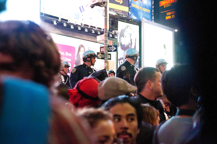 """Police officers on horseback overlook protesters with """"Occupy Wall Street"""" which are blocked by barricades in Times Square on October 15, 2011 in New York City.  While crowd estimates numbered in the tens of thousands, police tactics (including nets, motor scooters, barricades, arrests, and intimidation by riders on horseback) prevented the crowd, which had been split up, from joining together as one in the middle of Times Square."""