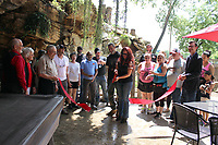 MEGAN DAVIS/MCDONALD COUNTY PRESS On Saturday, June 8, members of the McDonald County Chamber of Commerce gathered to celebrate as Teresa and Chris Ezzell cut the ribbon of The Cave Bar & Grill in Lanagan. The one-of-a-kind restaraunt serves fresh food and cold drinks in a natural environment with a view of The Cave's the beloved goats.
