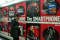 A man looks at his mobile phone in front of a smartphone advert in Tokyo, Japan.  From Bloomberg's 2010 report, iPhone is the top selling smartphone in Japan and is dominating the market with a 72% share, its biggest comptitors in Japan are HTC, which holds 11% of the smartphone market share, and Toshiba with a 6.8% market share. .09 Jan 2011