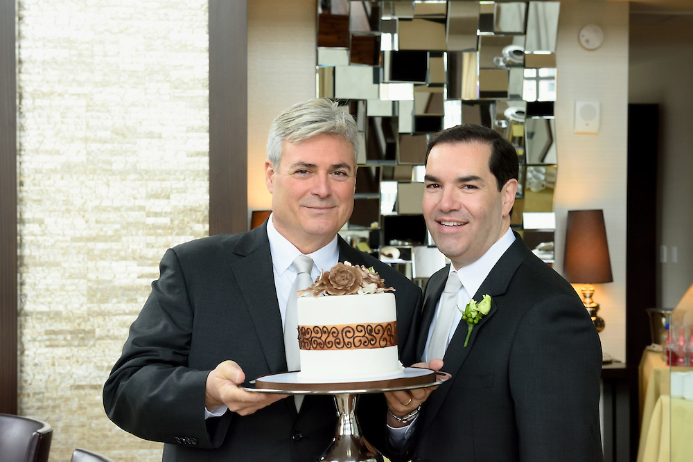 The two grooms holding the cake on a platter.