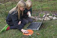 Junge und Mädchen, Kinder bestimmen Tiere und Pflanzen am Laptop im Garten mit einem digitalen Bestimmungsschlüssel, Bestimmungsübungen
