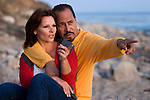 Mature couple sitting at beach, he pointing with concern