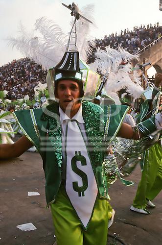 Rio de Janeiro, Brazil. Samba dancers during the carnival parade; greenback dollar $ and aircraft theme.