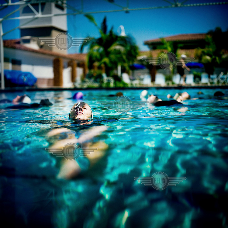 73 year old Margo Bouer practices with the Aquadettes in the swimming pool at Laguna Woods, California. Margo suffers from severe MS, but says her nausea and shaking almost disappear when she is in the swimming pool. She has been with the Aquadettes for 16 years. The Aquadettes are a group of women ageing from their early 60s upwards who meet to practice synchronised swimming. Every year, they practice together, they make costumes together, they swim together, and at the end, they perform together.