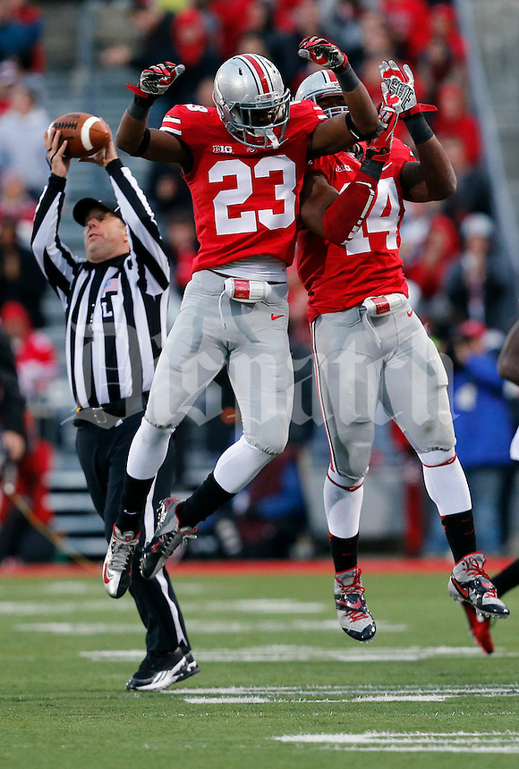 Ohio State Buckeyes defensive back Tyvis Powell (23) and Ohio State Buckeyes linebacker Curtis Grant (14) leaps fora  celebrations of Powell's interception in the fourth quarter of their game at Ohio Stadium in Columbus, Ohio on October 19, 2013. Columbus Dispatch photo by Brooke LaValley)
