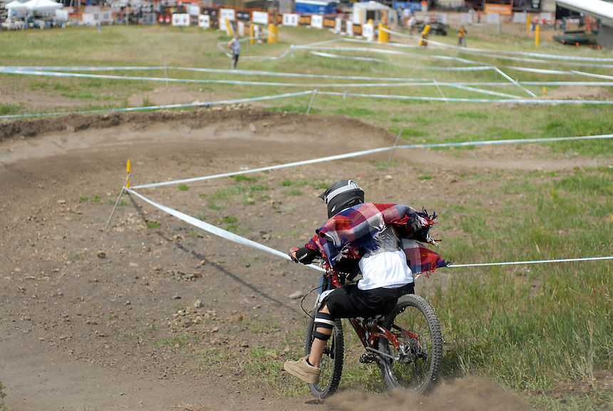 An amateur downhill mountain bike racer slips both pedals while practicing for a downhill mountain bike race at Sol Vista resort in Colorado.