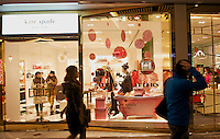 People walk past a newly opened Kate Spade store in Sanlitun, Beijing, China. 11-Jan-2014