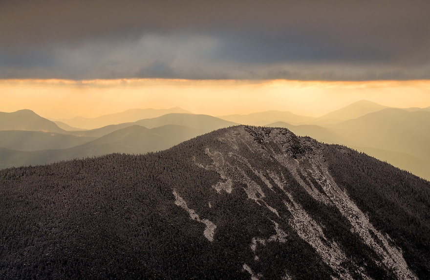 Golden light spills from the clouds behind Mt. Flume on  a cold november morning.