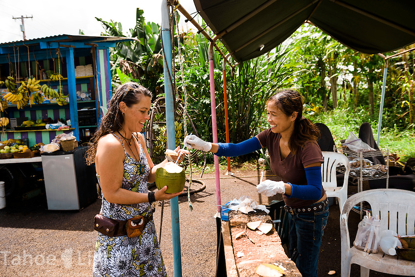 Monique gets her fresh coconut from a little fruit stand on the road near Akaka falls on the big island of Hawaii.