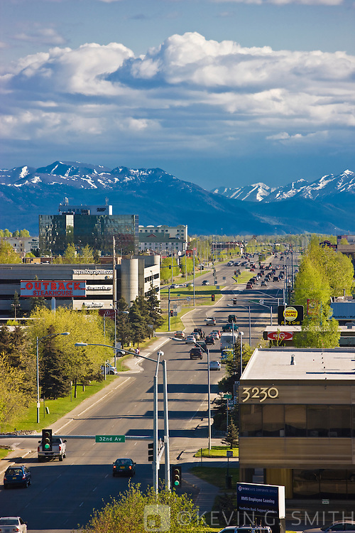 View of the highrise office buildings that make up midtown Anchorage, traffic heading south out of town, Kenai mountains in the background, spring foliage, Anchorage, Southcentral Alaska, USA.