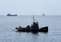 """Pictured: A Coastguard vessel near the oil spill that has reached the coast of Salamina, Greece<br /> Re: An oil spill off Salamina island's eastern coast is spreading and has become """"an environmental disaster"""" according to local authorities in Greece.<br /> The spill was caused by the sinking of the Aghia Zoni II tanker, carrying 2,200 metric tons of fuel oil and 370 metric tons of marine gas oil on Saturday, southwest of the islet of Atalanti near Psytalleia. According to reports, the coastline stretching from Kinosoura to the Selinia community has """"turned black"""" and authorities fear a new leak from the sunken ship.<br /> According to the island's mayor, Isidora Papathanasiou, the weather """"turned on Sunday afternoon and brought the oil spill to Salamina."""""""