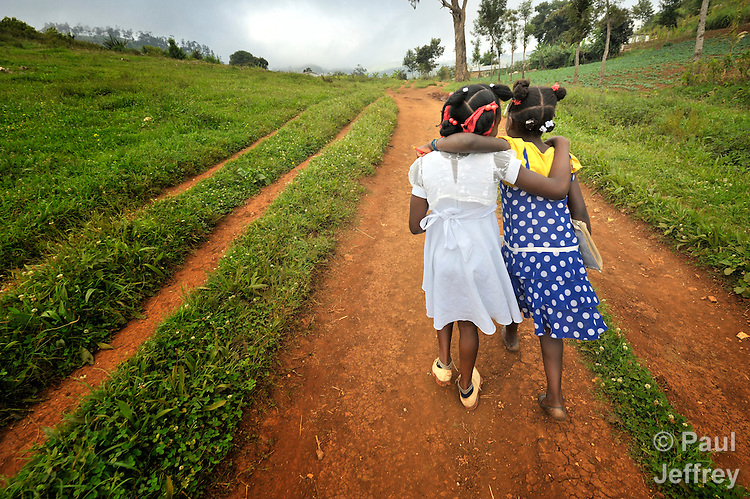 Two girls walk to school in the Haitian village of Foret des Pins.