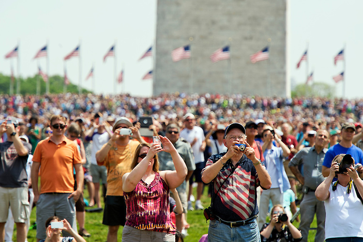 UNITED STATES - MAY 8: Spectator watch World War II era aircraft as they fly over the World War II Memorial on the Mall to commemorate the 70th anniversary of the victory in Europe, known as VE Day, May 8, 2015. (Photo By Tom Williams/CQ Roll Call)