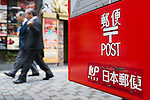 Pedestrians walk past a post mailbox in Shinjuku district on October 29, 2015, Tokyo, Japan. The share price for Japan Post Holdings Co. public offering was set at 1,400 yen (11.58) for its debut on the Tokyo Stock Exchange next November 4. This price was at the high end of expectations and the government hopes that many Japanese citizens will take the opportunity to invest in the company. (Photo by Rodrigo Reyes Marin/AFLO)