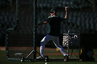 OAKLAND, CA - APRIL 17:  Coach Matt Williams #4 of the Oakland Athletics throws batting practice before the game against the Houston Astros at the Oakland Coliseum on Wednesday, April 17, 2019 in Oakland, California. (Photo by Brad Mangin)
