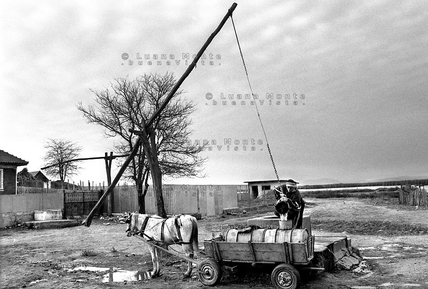 - Delta del Danubio, Enisala. Un ragazzo vicino al pozzo comune del villaggio, riempie la cisterna mobile montata sul suo carro.- Danube Delta Area, Enisala. Dan, near the common well of the village, maked the water tank on the cart full. The majority of the houses of the Danube Delta Area doesn't have running water...