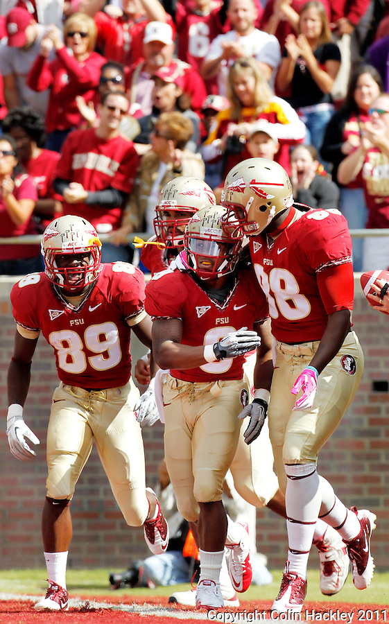 TALLAHASSEE, FL 10/29/11-FSU-NCST102911 CH-Florida State's Devonta Freeman, center, celebrates scoring the Seminole's first touchdown against N.C. State with Beau Reliford, right, and Christian Green during first half action Saturday at Doak Campbell Stadium in Tallahassee. .COLIN HACKLEY PHOTO