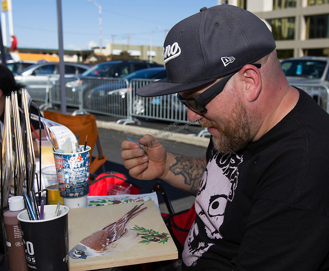 Seth McCorkle works on a painting at the Midtown Art Walk on Thursday afternoon in Reno, June 28, 2018.