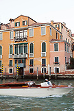 ITALY, Venice. A water taxi passes by in front of a home along the Grand Canal.