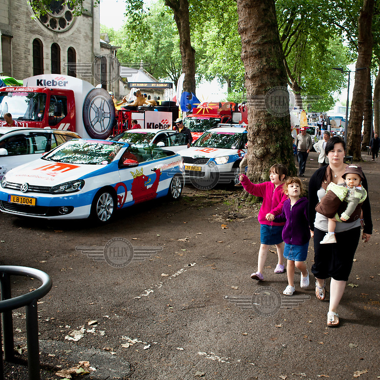 A mother walks with her children beside some of the many colourful vehicles that form the Tour de France Caravan. This parade, consisting of cars advertising various brands and goods, travels ahead of the actual race, along the race route. According to official Tour de France website, this parade has become an essential part of the race and as many as 47% of spectators come first and foremost to see the caravan..