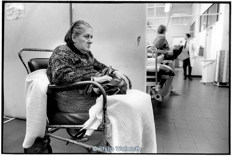 A woman in a wheelchair waits for treatment in the Accident and Emergency Department of Kings College Hospital, London.