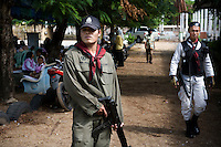 Heavily armed police guards outside the remainings of the Datoa school. The children are sitting outside under the trees because the school building has been burned down by the militia just two weeks before. Thailand is struggling to keep up appearances as the land of smiles has to face up to its troubled south. Since 2004 more than 3500 people have been killed and 4000 wounded in a war we never hear about. In the early hours of January 4th 2004 more than 50 armed men stormed a army weapons depot in Narathiwat taking assault rifles, machine guns, rocket launchers, pistols, rocket-propelled grenades and other ammunition. Arsonists simultaneously attacked 20 schools and three police posts elsewhere in Narathiwat. The raid marked the start of the deadliest period of armed conflict in the century-long insurgency. Despite some 30,000 Thai troops being deployed in the region, the shootings, grenade attacks and car bombings happen almost daily, with 90 per cent of those killed being civilians. 24.09.07. Photo: Christopher Olssøn