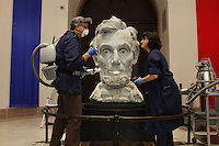 """NEW YORK - SEP 24: Alan Balicki, the Chief Conservator, and Elizabeth Fiorentino, the Registrar, surface clean the Lincoln Head Sculpture at the New-York Historical Society in New York on Thursday, September 24, 2009.  The bust of Lincoln will welcome visitors to the major new exhibition """"Lincoln and New York,"""" at the New- York Historical Society. The plaster bust of Abraham Lincoln was made in 1922 by artist Daniel Chester French as a full-scale maquette for his Lincoln Memorial sculpture in Washington, DC. Measuring 43 ¾ inches in height, the maquette is being installed on a low pedestal, to give visitors a startling eye-level view of the familiar head, which in the Memorial looms far above them. Christopher Alzapiedi is the exhibitions tech, who is standing on the Genie, working on the lighting for the bust. (Photo by Landon Nordeman)"""
