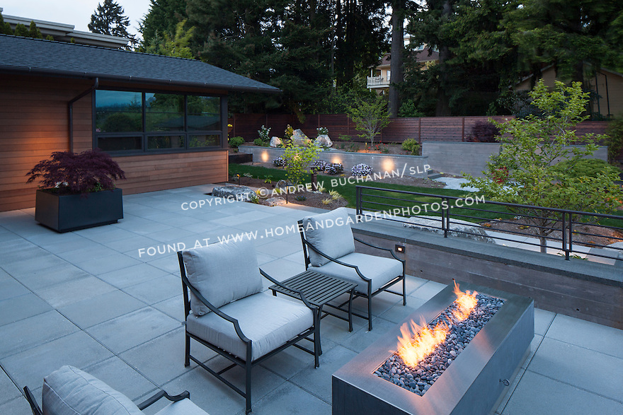 A large patio with outdoor firepit offers a place to enjoy a summer evening.