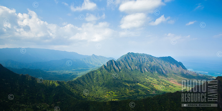 An aerial panorama of Kualoa Valley on a voggy day, Windward O'ahu, with the ocean and continuing Ko'olau Mountain Range in the distance.