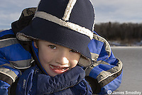 Happy young boy lying down on the frozen lake ice