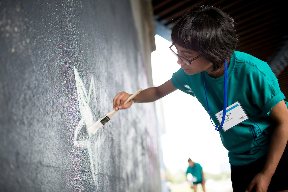 """Shirasa Prajapati paints a mural under a train bridge during """"Circle the City with Service,"""" the Kiwanis Circle K International's 2015 Large Scale Service Project, on Wednesday, June 24, 2015, in Indianapolis. (Photo by James Brosher)"""