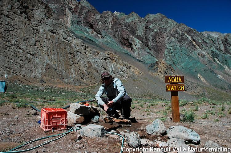 Mann vasker opp i campen Confluencia på Aconcagua. ---- Man washing a kettle in camp Confluencia on Aconcagua.