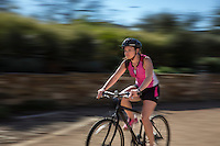 Young attractive female bike cyclist rides along the Lady Bird Lake Hike and Bike Trail, (intentional motion blur).