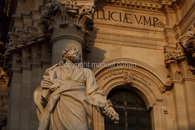 Statue of St Peter holding a key and a book, in front of the Baroque facade of Syracuse cathedral or Duomo, rebuilt in the 18th century, Ortygia Island, Syracuse, Sicily, Italy. The island is also known as the Citta Vecchio, as it is the old town of Syracuse and contains many historical buildings. Syracuse was founded in 734 BC and was a thriving city in ancient Greek times, and the birthplace of Archimedes. Much of Syracuse was rebuilt after the earthquake of 1693 and the Sicilian Baroque style is therefore prevalent. The old town of Syracuse is listed as a UNESCO World Heritage Site. Picture by Manuel Cohen