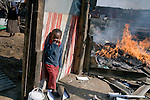 REIGER PARK, SOUTH AFRICA - MAY 23: A child stands in a destroyed shack on May 23, 2008 at the Ramaphosa squatter camp outside Johannesburg, South Africa. Locals chased out African immigrant in the area and many shacks were burned down during xenophobic attacks in the township. A man was burned alive down the street and thousands of people fled to a nearby police station for safety. (Photo by: Per-Anders Pettersson/Getty Images)..