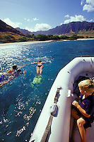 Family snorkeling off Oahu's Makua Beach in clear blue water