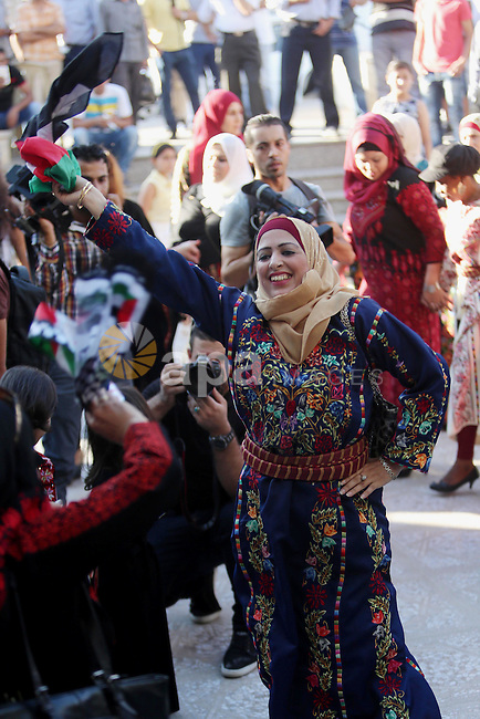 Palestinians perform a traditional dance during a ceremony of Palestinian Traditional Dress and Heritage Day in the West Bank city of Ramallah, on July 25, 2016. Photo by Shadi Hatem
