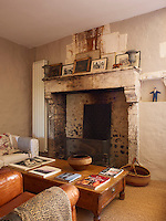 The original fireplace in the living room has been restored and family photographs are displayed on the mantelpiece