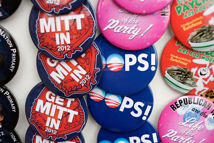 A man sells buttons with anti-Obama, pro-Romney and pro-conservative messages outside a Mitt Romney town hall meeting and rally at the Rochester Opera House in Rochester, New Hampshire, on Jan. 8, 2012. Romney is seeking the 2012 Republican presidential nomination.