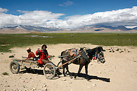"China has started building a controversial 67-mile ""paved highway fenced with undulating guardrails"" to Mount Qomolangma, known in the west as Mount Everest, to help facilitate next year's Olympic Games torch relay./// Two Tibetan men on a horsecart near the road to Everest.<br /> Tibet, China.<br /> July, 2007"