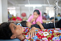 Workers of Tuba garments become to suffer from the consequences of the hunger. They are being helped with  intravenous saline drips inside the garments factory. Dhaka, Bangladesh