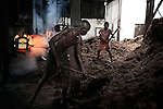 LUKUTU, DEMOCRATIC REPUBLIC OF CONGO MARCH 17: Unidentified men through in waste in a fire on March 17, 2006 in Lukutu, Congo, DRC. The steam engines run most of the palm oil factory in this small village along the Congo River, about 1500 kilometers from Kinshasa, the capital. The factory is a big producer of palm oil, which is used for cooking. The Belgians built the factory in 1911 and it was closed during the recent civil war. About 10,000 people are dependent on the factory, the only one in the area. Congo River is a lifeline for millions of people, who depend on it for transport and trade. During the Mobuto era, big boats run by the state company ONATRA dominated the traffic on the river. These boats had cabins and restaurants etc. All the boats are now private and are mainly barges that transport goods. The crews sell tickets to passengers who travel in very bad conditions, mixing passengers with animals, goods and only about two toilets for five hundred passengers. The conditions on the boats often resemble conditions in a refugee camp. Congo is planning to hold general elections by July 2006, the first democratic elections in forty years. (Photo by Per-Anders Pettersson)
